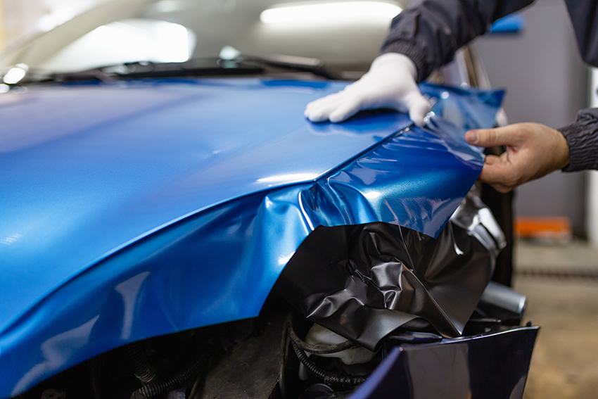 Car bonnet being wrapped in blue vinyl