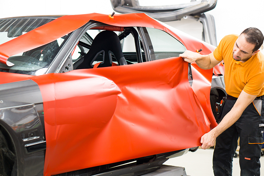 car door being wrapped in orange vinyl